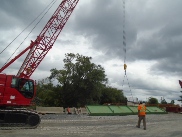 Cut girder piece being lowered onto the site