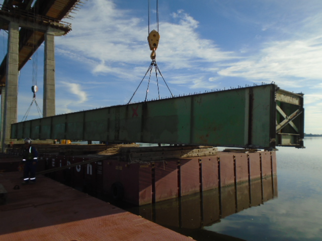 First girder section being placed on the barge