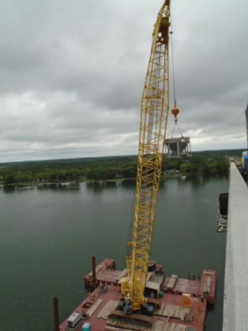 Crane lifting concrete hopper in preparation for concrete placement