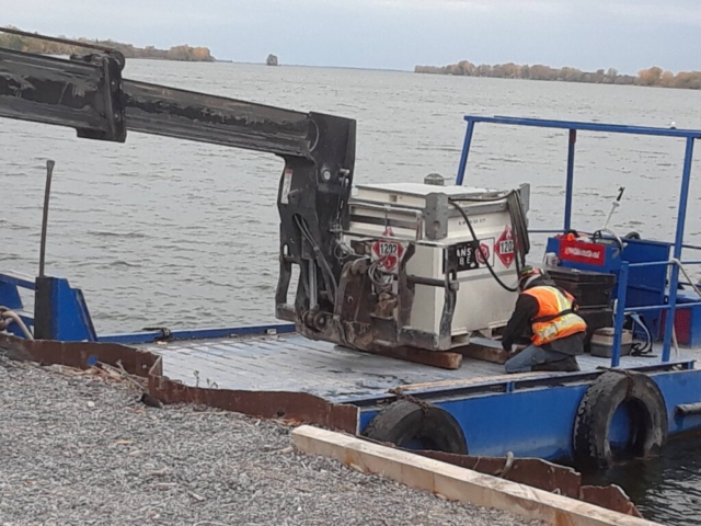 Telehandler loading the fuel cell onto the boat to be taken out to the barge
