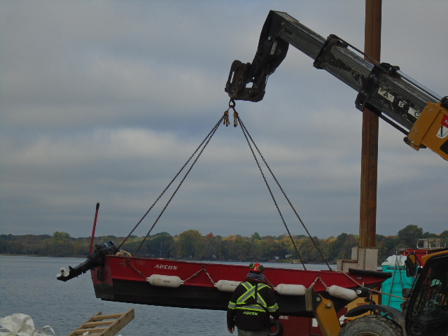 Using the telehandler to lower the boat onto the water