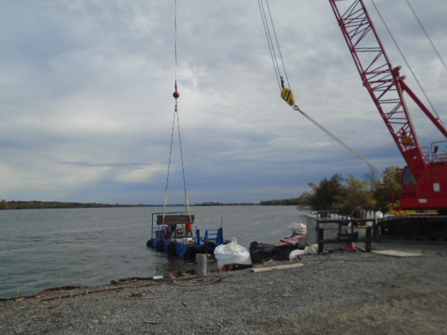 110 ton crane lowering wood onto the boat to be take to the barge