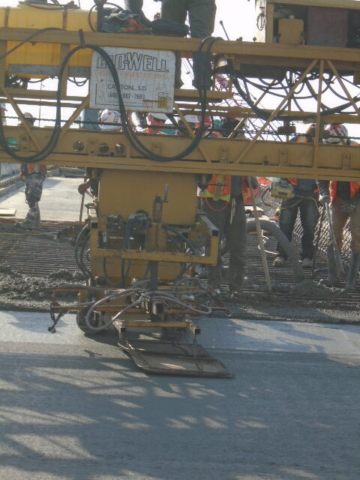 Close-up of the concrete finisher evening out the concrete