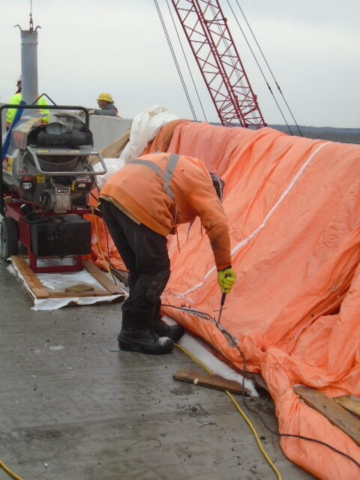 Removing the tarping from the newly placed barrier wall