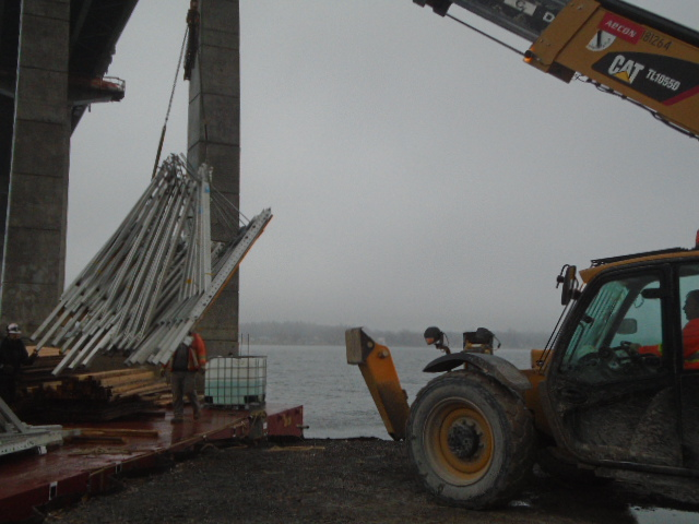 Removing the support brackets from the barge with the telehandler