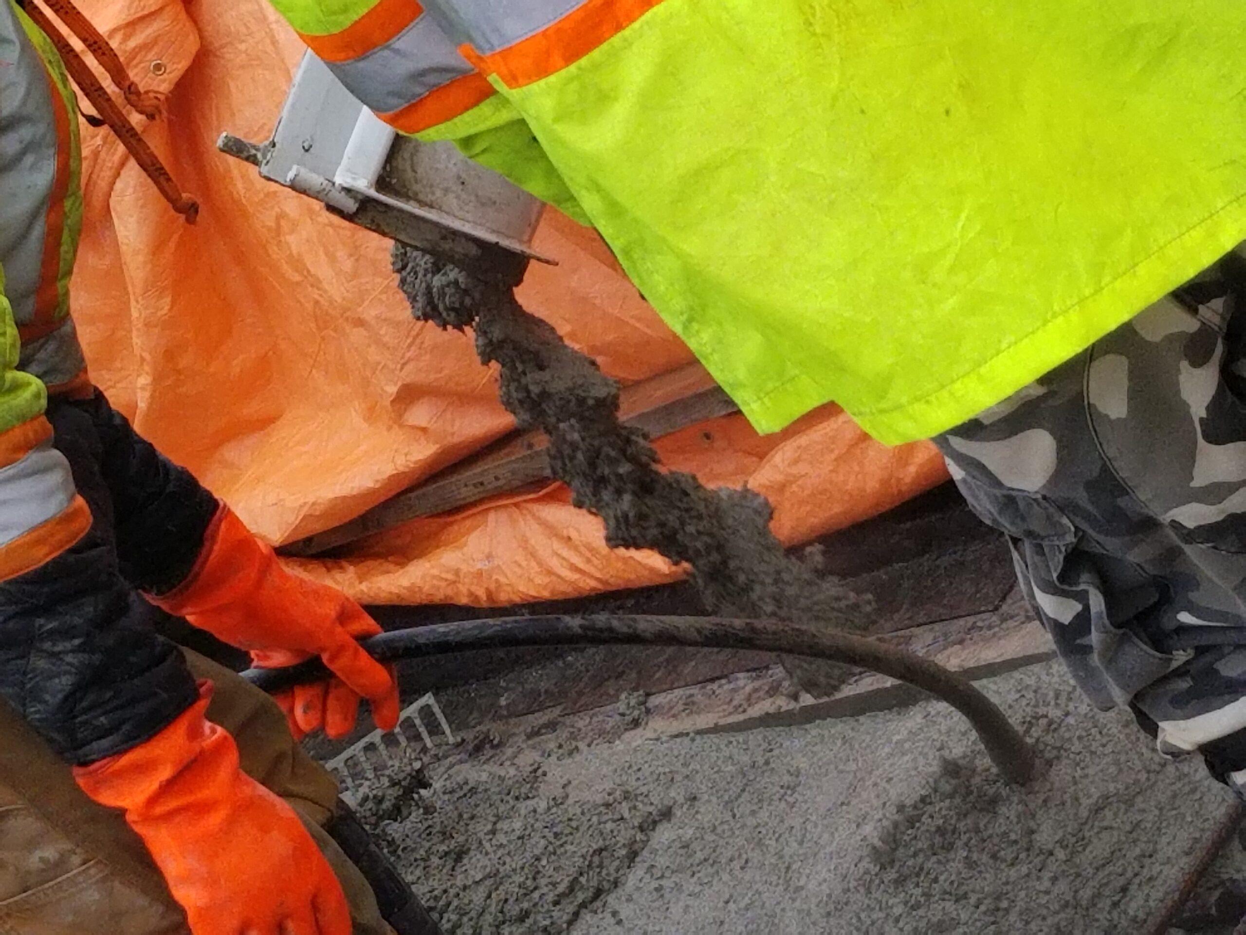Close-up of closure strip concrete placement, vibrating the concrete