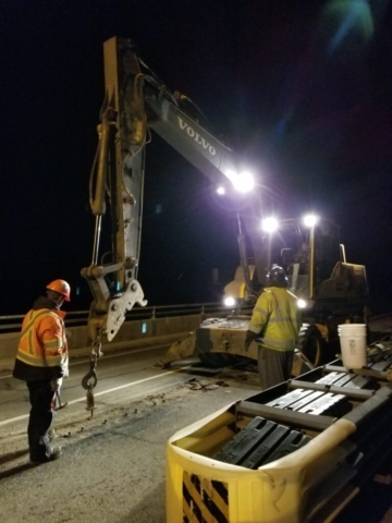 Excavator removing the bolts from the deck