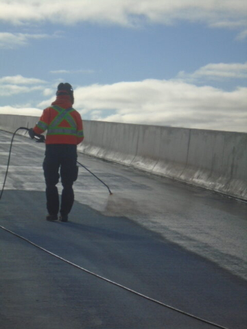Applying tack coat primer to the concrete deck for waterproofing application