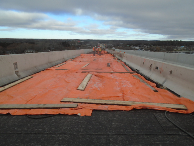 Covering the glycol lines with tarps to contain heat on the deck