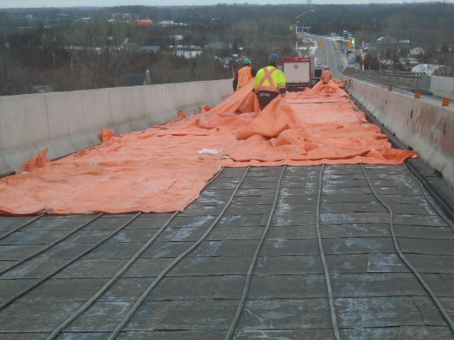 Removing the tarping for asphalt placement