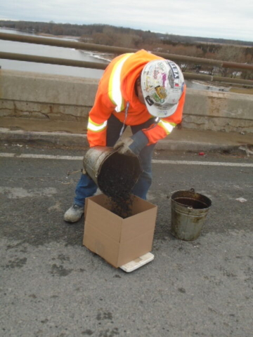 Asphalt being placed in box to be sent for testing