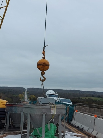 Concrete hopper hooked up to the 200 ton crane in preparation for concrete placement