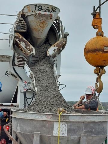 Concrete truck filling the hopper for concrete placement