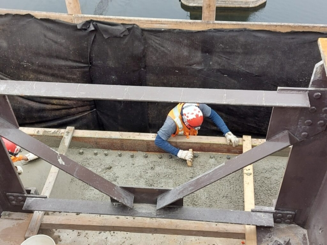 Smoothing the freshly placed concrete on pier cap 11