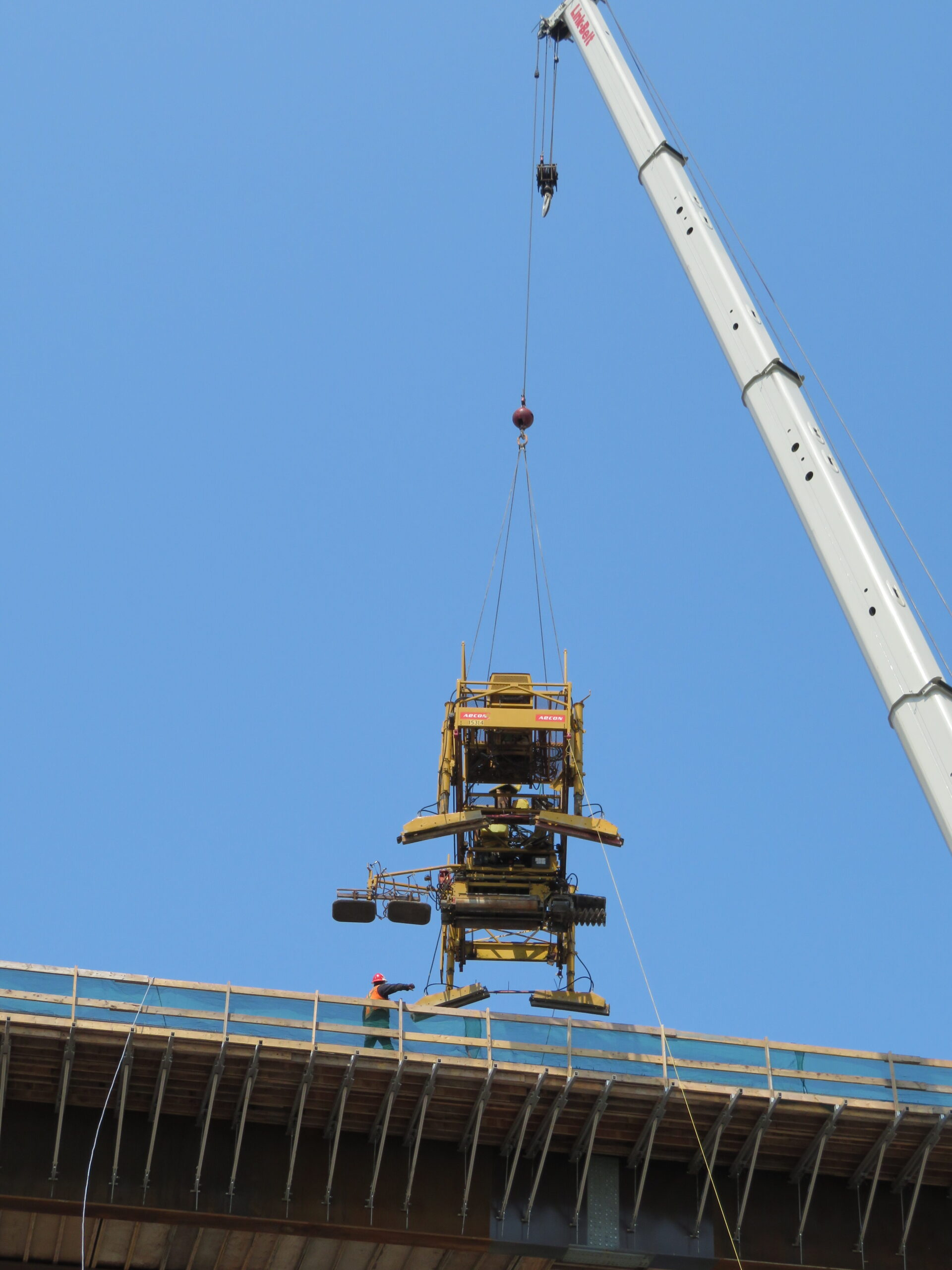Lowering the concrete finisher onto the deck