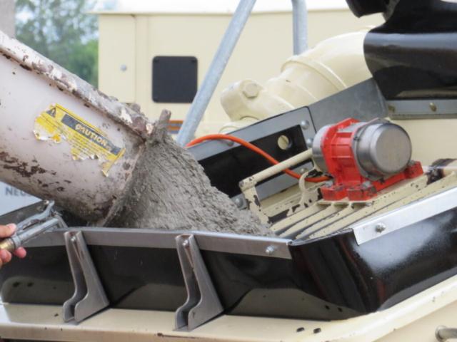 Concrete truck placing concrete into the concrete pump
