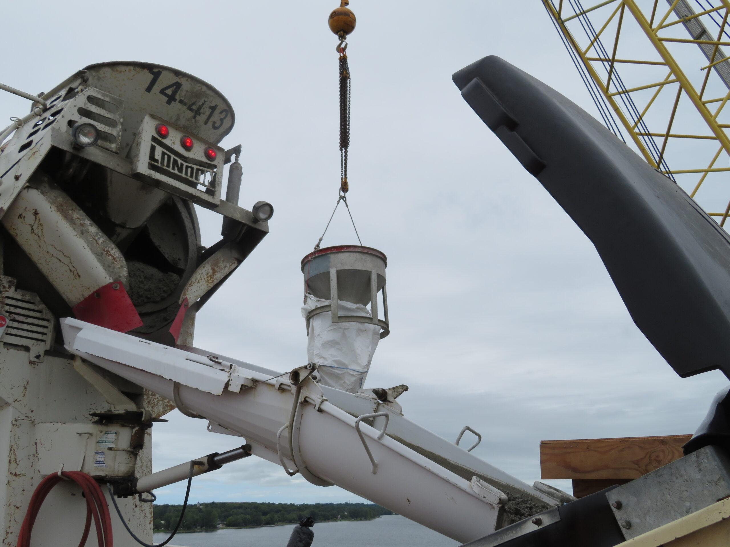 Close-up of concrete truck truck filling the pump truck, 200-ton crane lifting the hopper