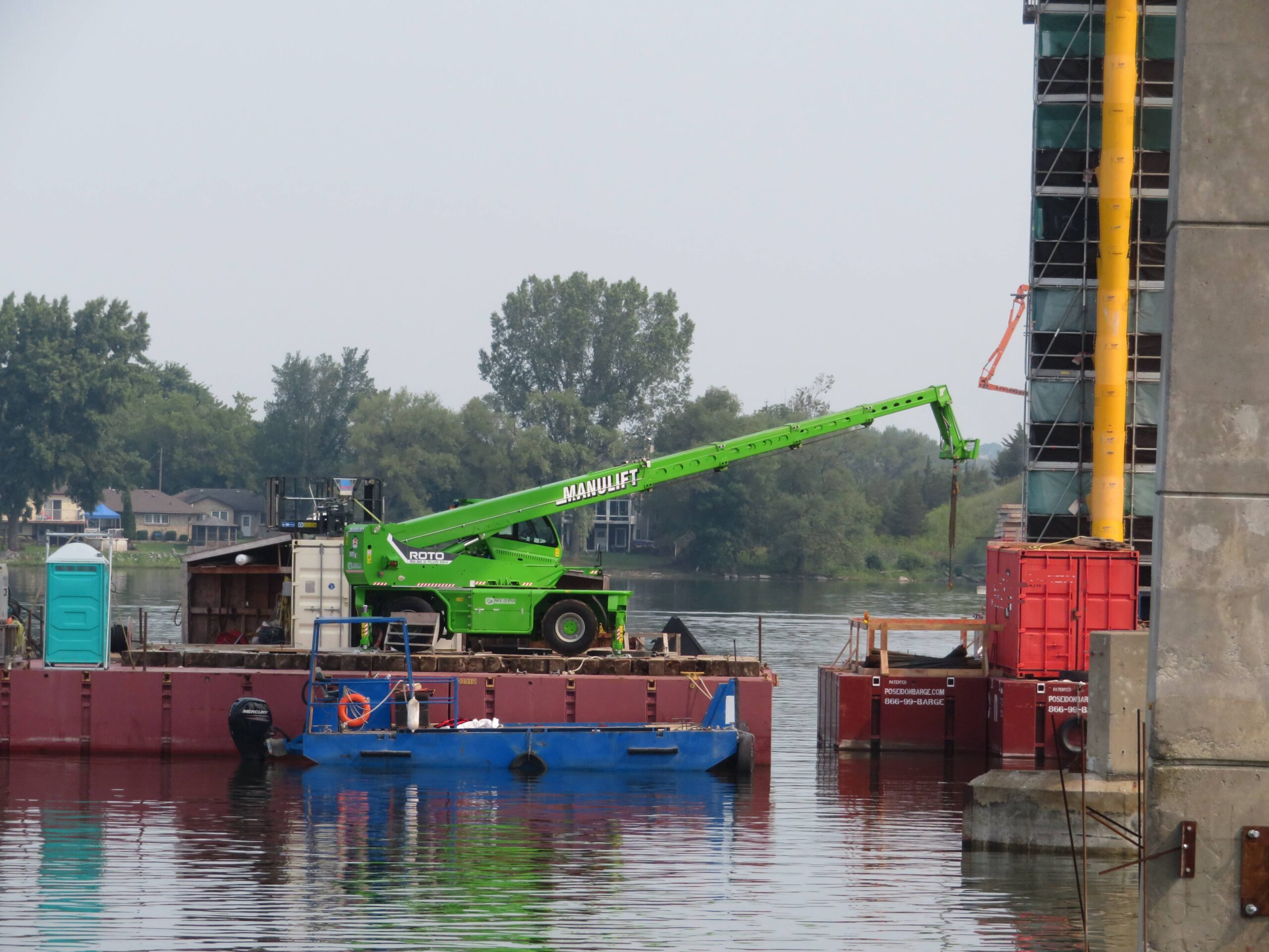 Using the manlift to move materials onto the pier 10 barge