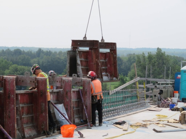Top view of the barrier wall formwork being lowered into place