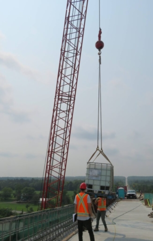 110-ton crane lowering the water tote containing burlap onto the deck
