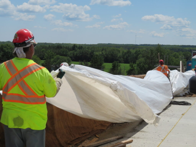 Placing plastic over the wet burlap on the new barrier wall section
