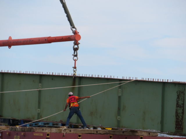 Using the tag lines to help lower the girder section to the barge