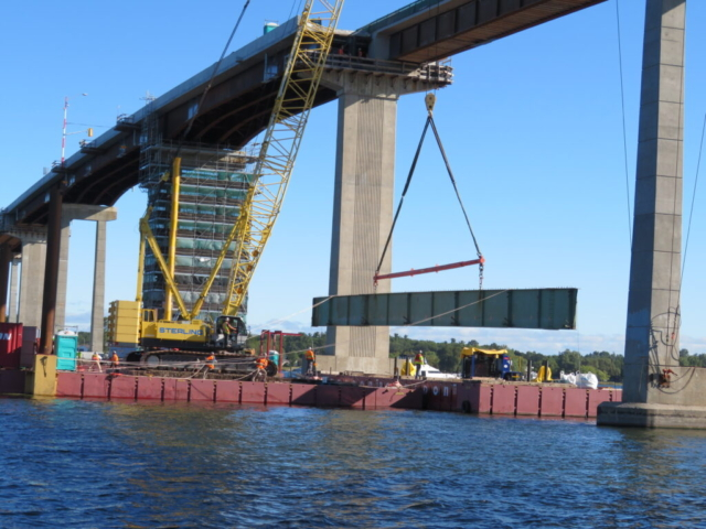 Lowering the girder section onto the barge, using tag lines to help guide the girder section