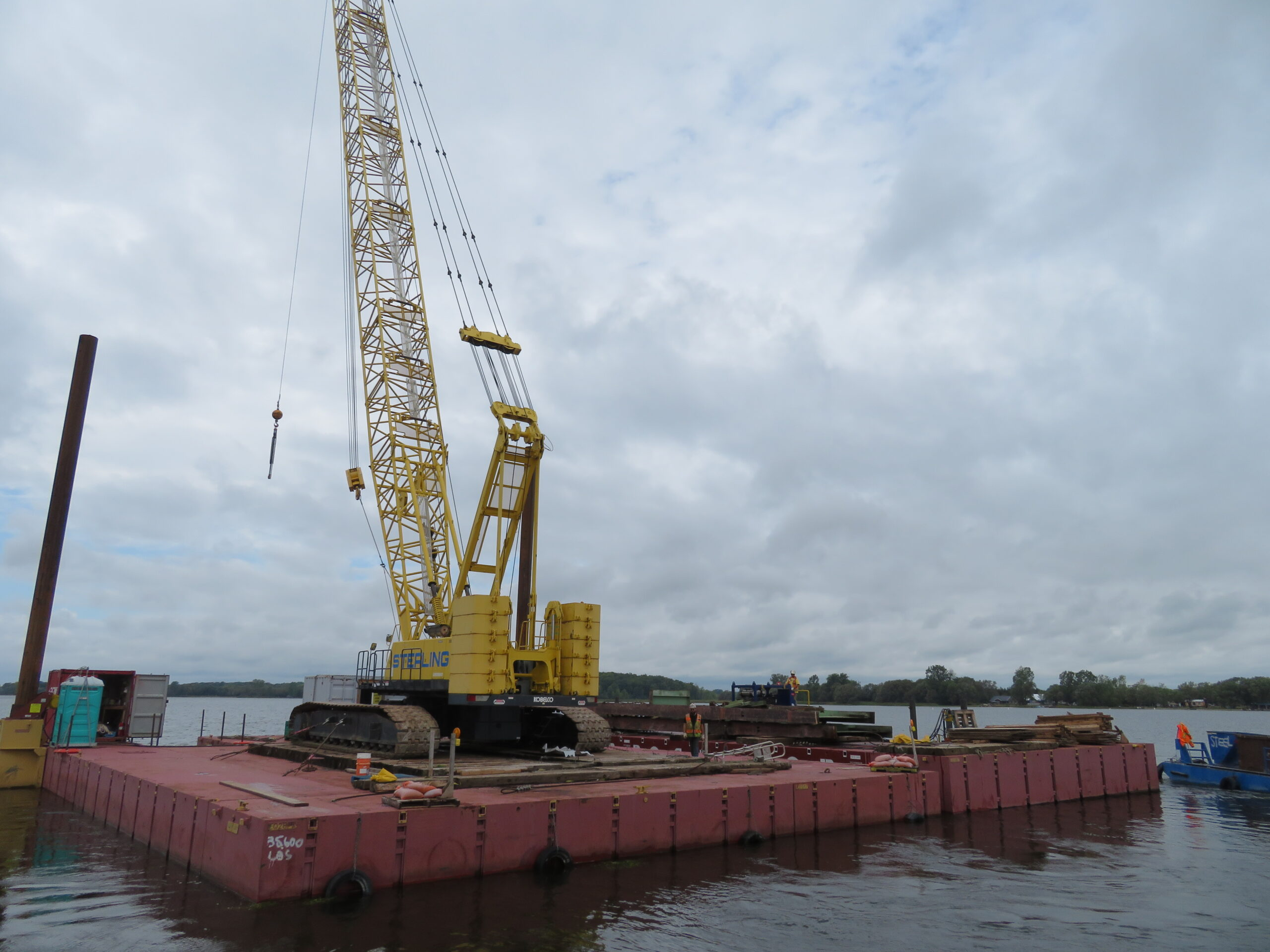 Removed girder sections being brought to the dock to be removed from the barge